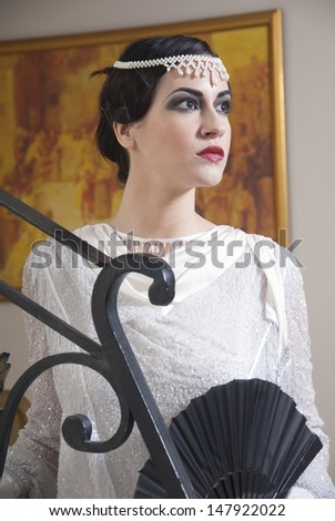Pretty girl wearing make-up in the style of 1920 - stock photo