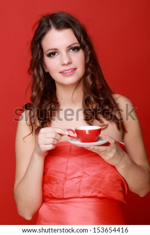 Pretty girl with beautiful healthy hair drinking coffee from a red cup/Attractive young woman in evening dress drink coffee on a red background - stock photo