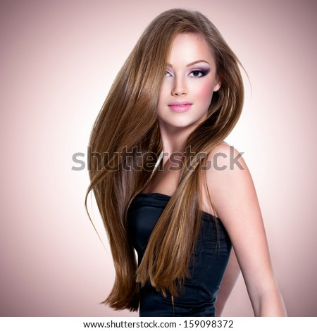 Pretty girl with beautiful long straight  hair and attractive face looking at camera - stock photo