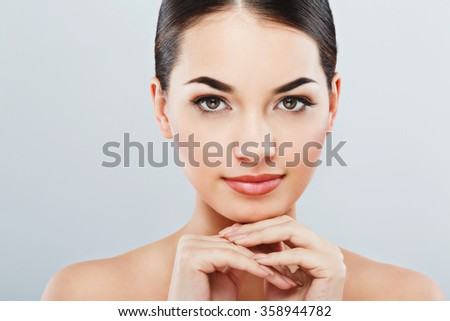 Pretty girl with big eyes and dark eyebrows, with naked shoulders, looking at camera and smiling, holding hands near face, light nude make-up, gray studio background, beauty photo, close up - stock photo