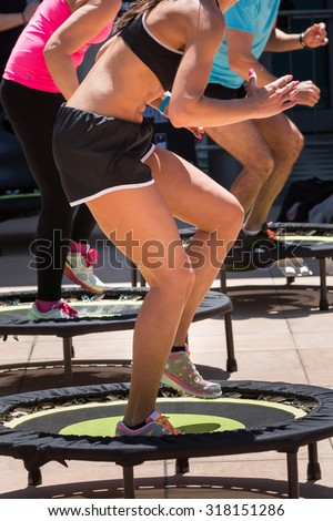 Pretty Girl with Black Top and Shorts Sportswear Having Exercise on Rebounder in Class at Gym - stock photo