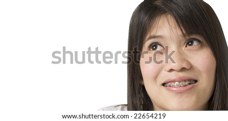 Pretty girl with braces looking up - stock photo