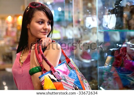 Pretty girl with colorful bag in the shop - stock photo