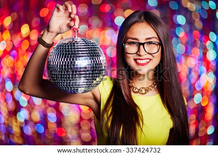 Pretty girl with disco ball and toothy smile looking at camera - stock photo