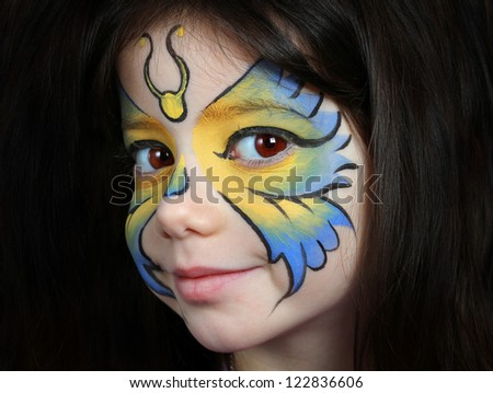 Pretty girl with face painting of a butterfly - stock photo