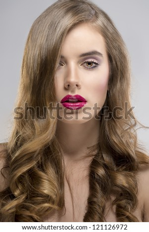 pretty girl with flowing wavy hair and purple make-up, she is in fornt of the camera, looks in to the lens - stock photo