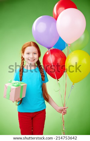 Pretty girl with giftbox and balloons looking at camera in isolation - stock photo