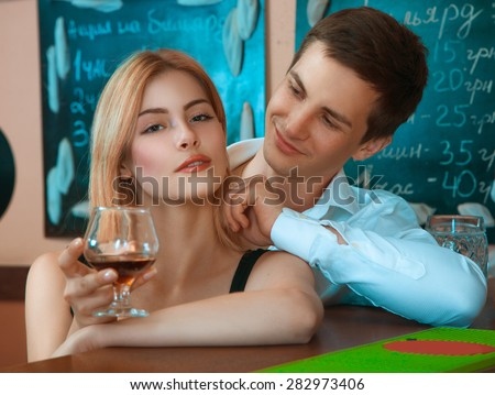 pretty girl with glass of wine and hugs her boyfriend from behind at bar. horizontal photo - stock photo