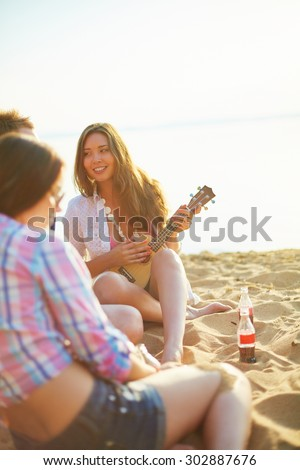 Pretty girl with guitar looking at her friend while sitting on sandy beach - stock photo