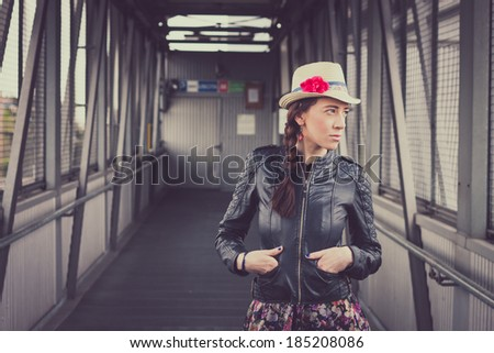 Pretty girl with hat and black leather jacket posing