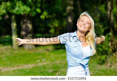 Pretty girl with her arms outstretched having fun at the summer park - stock photo