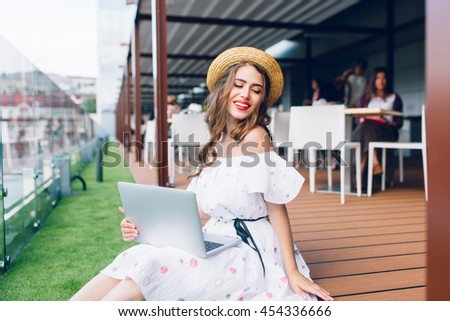 Pretty girl with long hair is sitting on flor on the terrace. She wears a white dress with bare shoulders, red lipstick and hat . She holds a laptop on knees and smiling.