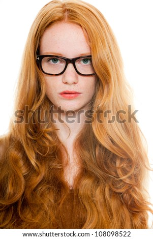 Pretty girl with long red hair wearing brown shirt and vintage glasses. Fashion studio shot isolated on white background.