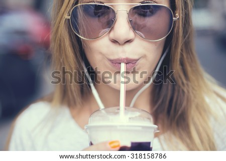 pretty girl with milk shake listening music on the street. Sunset