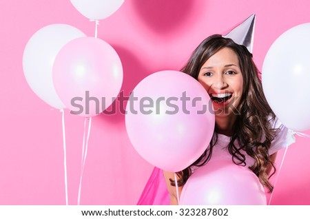 Pretty girl with party hat with balloons on pink background, birthday party celebration