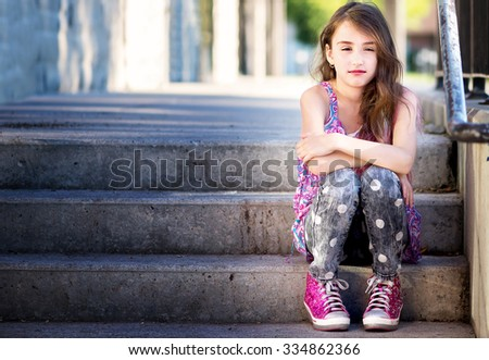 Pretty girl with pink hair sitting on steps with her arms crossed - stock photo