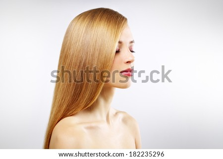 Pretty girl with straight hair on a gray background - stock photo