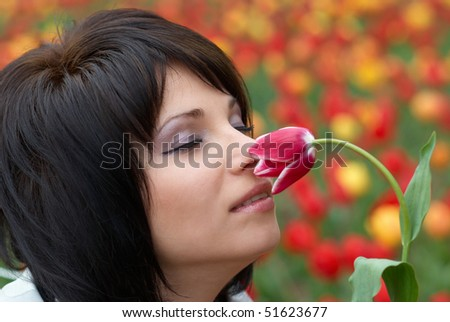 Pretty girl with tulip with flowers background - stock photo