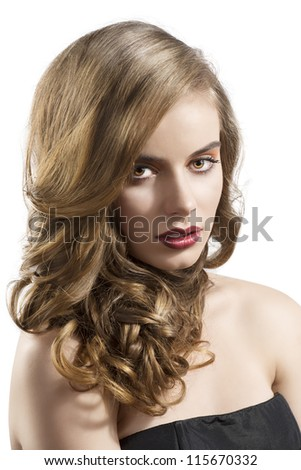 pretty girl with wavy hair and red lipstick, she is turned of three quarters at left looks in to the lens with hair on the right shoulder