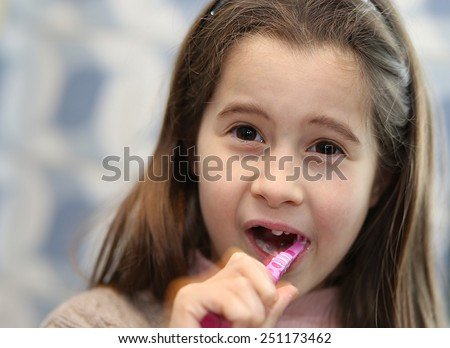 pretty girl without a tooth while brushing teeth in the bathroom - stock photo
