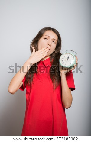 pretty girl yawning with an alarm clock in a red dress, studio, isolated - stock photo