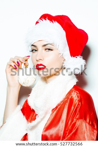 Pretty girl young beautiful cute woman sexy female model in traditional santa claus new year red hat and suit poses with Christmas bauble isolated on white