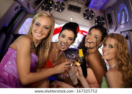Pretty girls celebrating in limousine, clinking glasses, smiling.