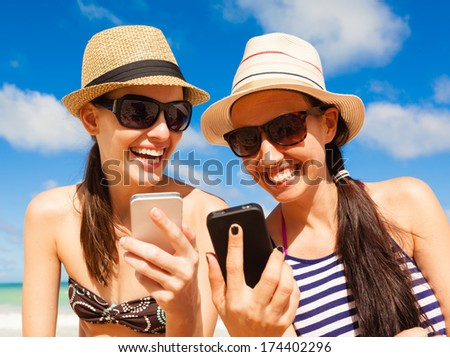 Pretty girls using smart phone on the beach. Summer holiday, technology and beach concept. - stock photo