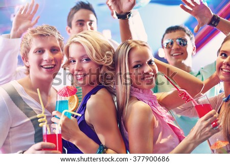 Pretty girls with cocktails at party and happy friends near by - stock photo