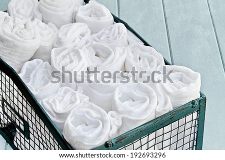 Pretty green basket filled with neatly organized rolled up cleaning rags. Shallow depth of field. - stock photo