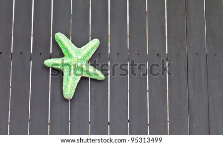 Pretty green starfish on boardwalk - stock photo