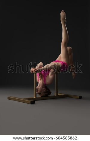 Pretty gymnast posing slenderly on special stand
