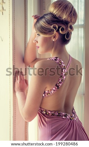 pretty hairstyle with bun and curls - stock photo