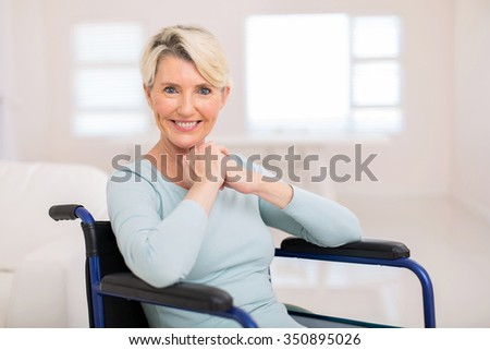 pretty handicapped middle aged woman sitting in wheelchair - stock photo