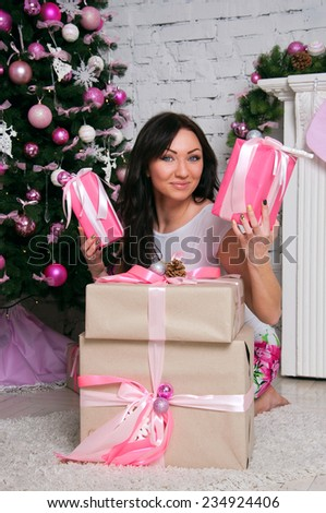 Pretty happy brunette woman wearing an elegant white dress, sitting near a decorated Christmas tree and a fireplace, holding many presents, smiling, looking at camera. - stock photo