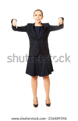 Pretty happy businesswoman pointing down - stock photo