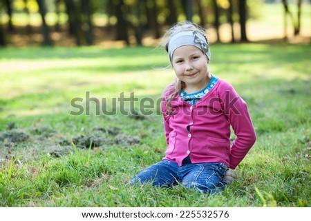 Pretty happy Caucasian girl portrait, sitting on kneels on grass, copyspace - stock photo