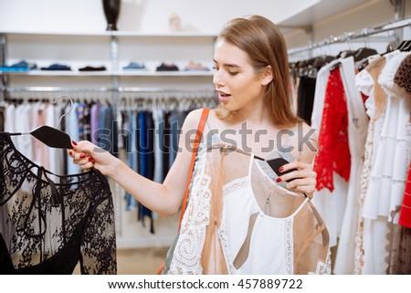 Pretty happy young woman choosing between two dresses in clothing shop