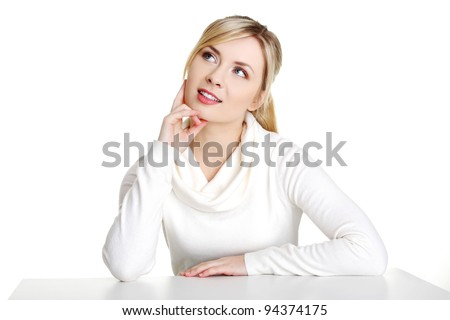 Pretty, happy, young woman in casual clothes sitting at the desk, isolated on white - stock photo
