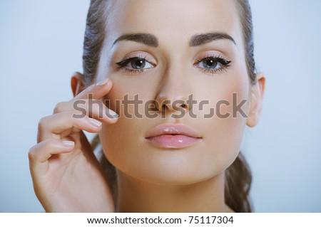 pretty healthy girl touches the skin around the eye - stock photo