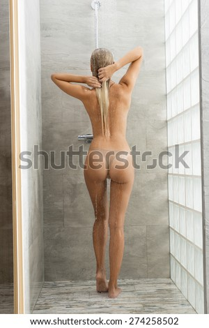 Pretty, healthy, sexy, feresh woman with long blonde hair is taking a shower, she is standing back of. She is holding her hair.
