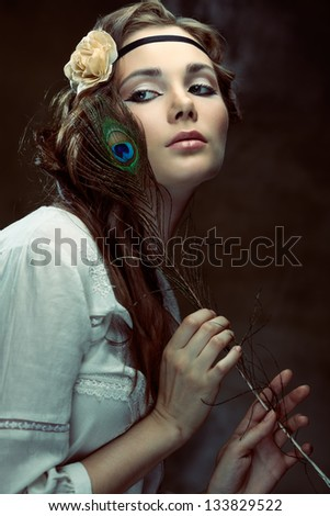 Pretty hippie girl posing with a peacock feather on grunge background - stock photo