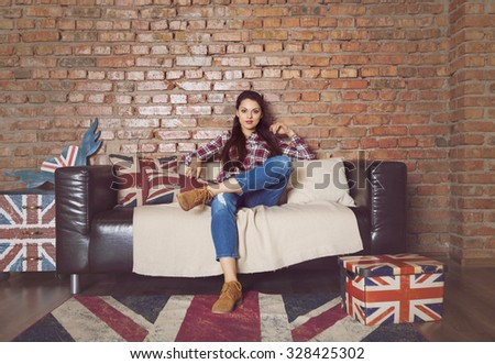Pretty hipster girl sitting on couch at home in the living room - stock photo