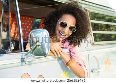 Pretty hipster leaning out van window on a summers day - stock photo