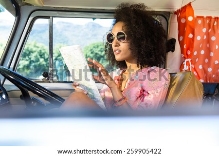 Pretty hipster looking at map in camper van on a summers day - stock photo