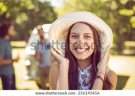 Pretty hipster smiling at camera on a summers day