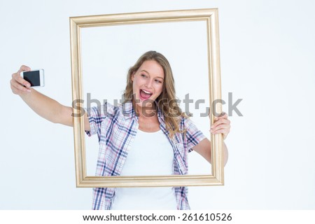 Pretty hipster taking selfie with smartphone on white background - stock photo