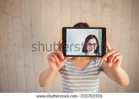 Pretty hipster taking selfie with tablet on wooden planks background - stock photo