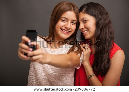Pretty Hispanic teenage friends taking a selfie with a smart phone