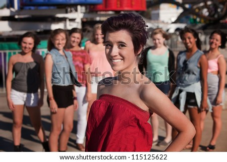 Pretty Hispanic teenage girl in front of group friends - stock photo